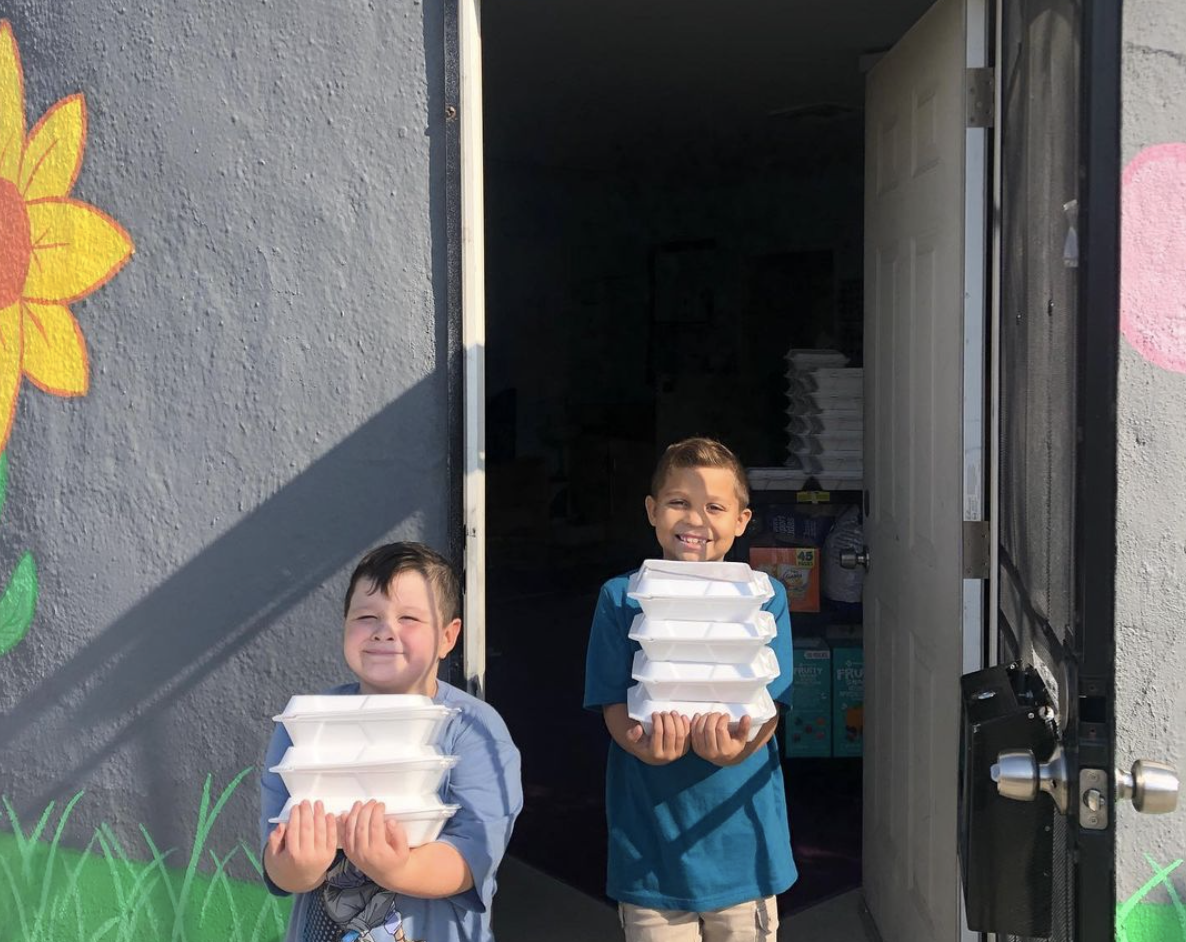 Two boys are carrying take-out containers of food to feed the kids at The Learning Box.