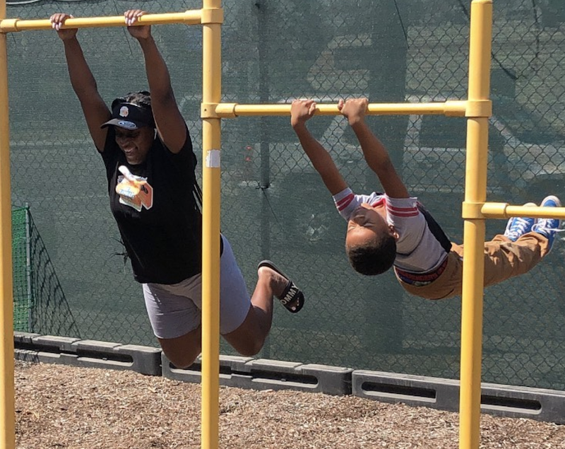 Teacher and child are swinging on the jungle gym.