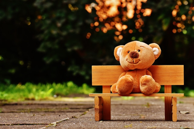 A stuffed teddy bear is sitting on the bench in the park.