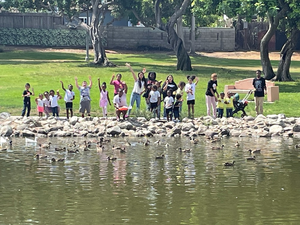 Kids are waving hands and smiling for a picture while standing around a pond at the park.